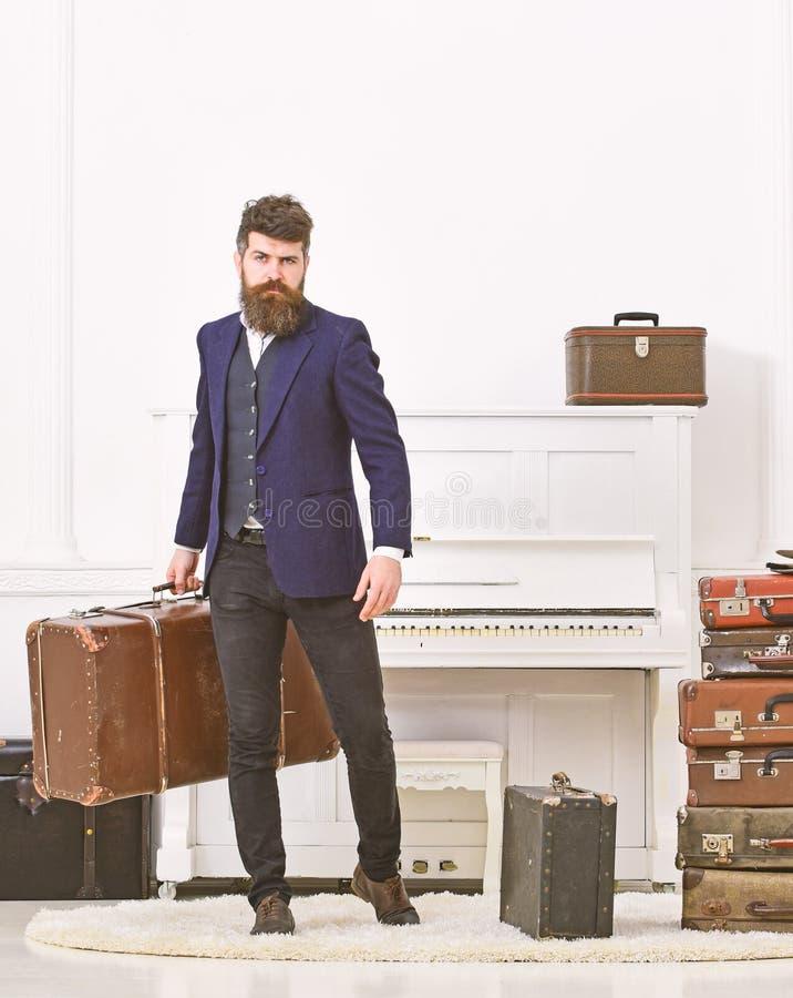 Man, handelsresande med skägget och mustasch med bagage, lyxig vit inre bakgrund Bagage och semesterbegrepp arkivbild