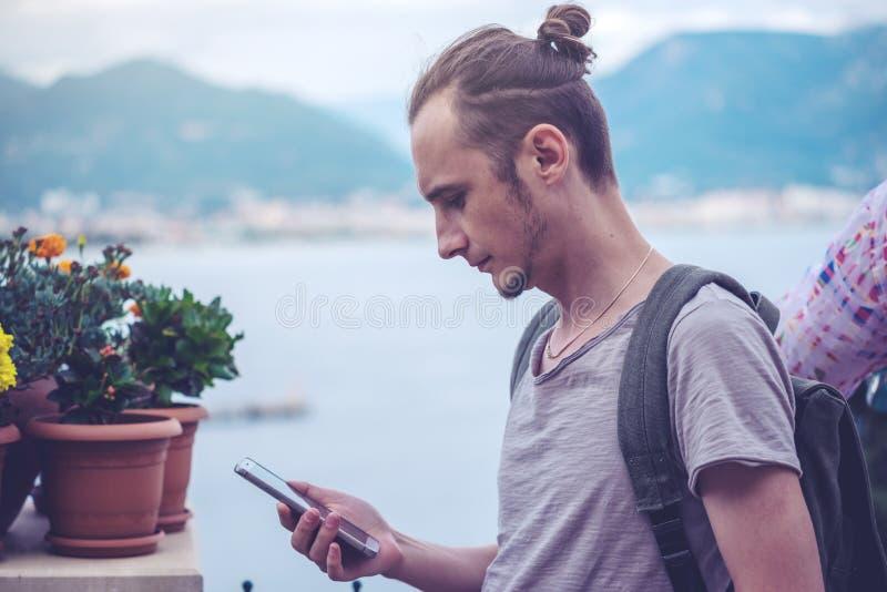 Man handelsresanden med ryggsäcken som ser hans smartphone på bakgrunden av naturen och bergen royaltyfria bilder