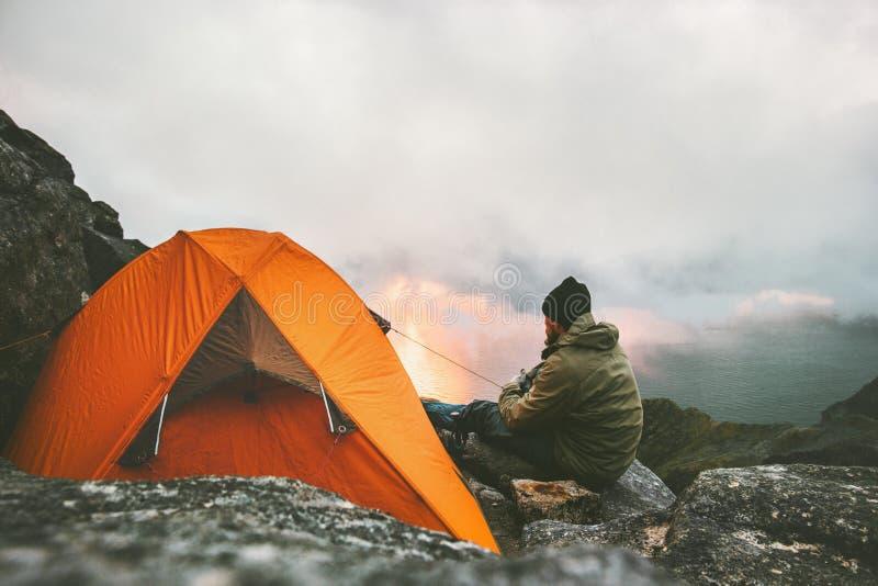 Man handelsresanden som nära kopplar av i berg av att campa för tält arkivfoton