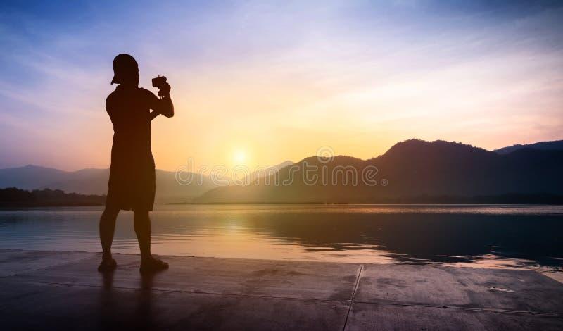 Man handelsresanden som tar foto av solnedgången på berg- och flodländer royaltyfria foton