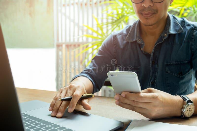 Man handen die celtelefoon met behulp van terwijl het werken met laptop aan houten bureau stock foto's