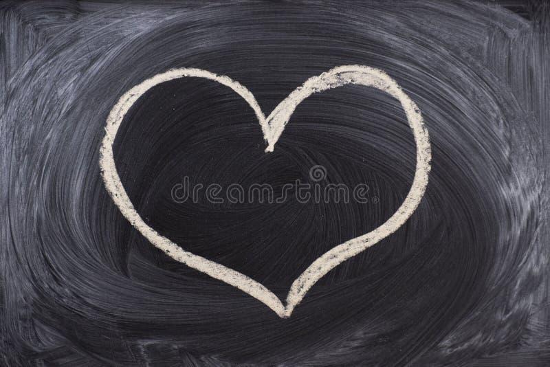 Man handen som drar en hjärta med krita i en svart tavla arkivfoto