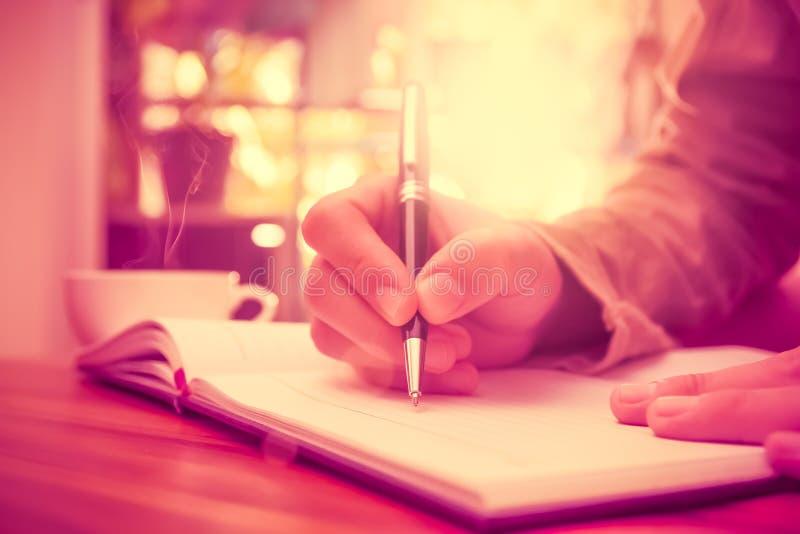 Man handen som rymmer en pennhandstil på anteckningsboken royaltyfria bilder