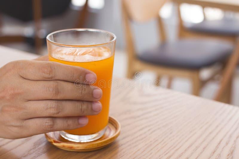 Man handen som rymmer ett exponeringsglas av orange fruktsaft arkivfoton