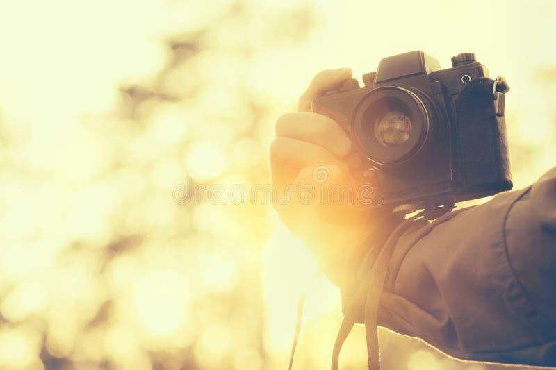 Man handen som rymmer livsstil för hipster för retro fotokamera utomhus- royaltyfri foto