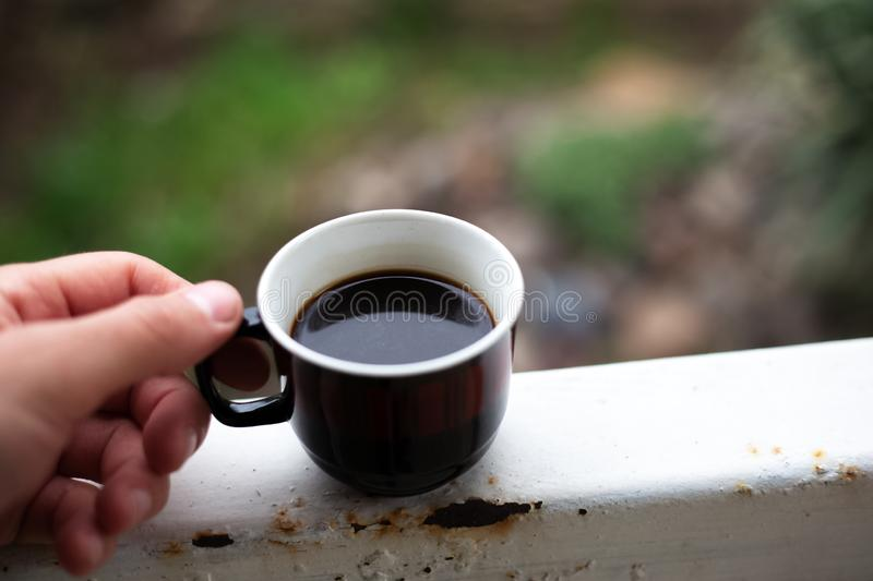 Man handing a cup of coffee in the garden stock images