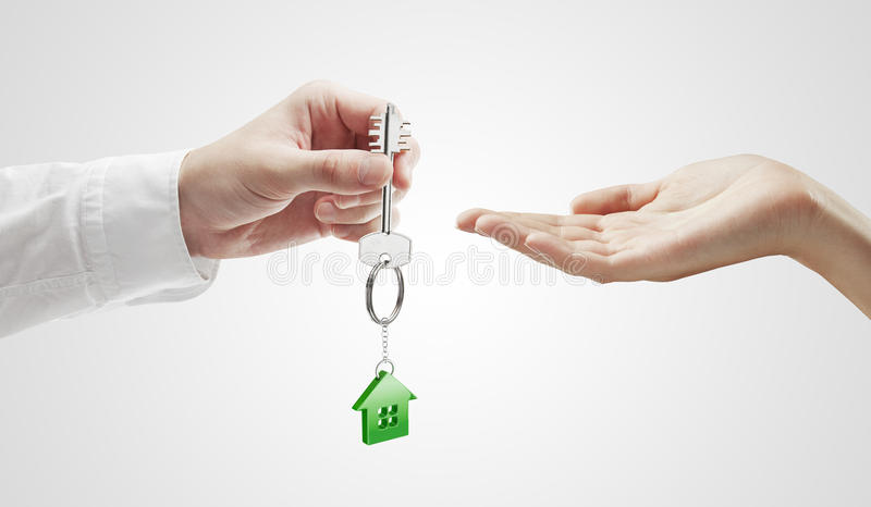 Man is handing a house key to a woman royalty free stock image
