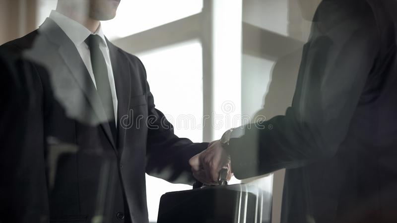 Man handing over briefcase to another man in business suit, secret transfer. Man handing over briefcase to another men in business suit, secret transfer, stock royalty free stock images