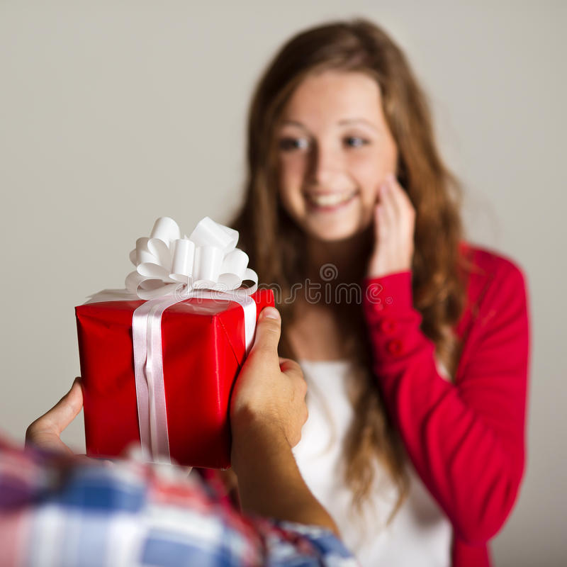 Man handing woman gift. Man handing red wrapped gift to a beautiful woman royalty free stock images