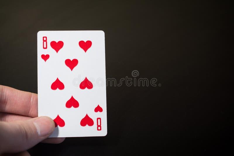 Man handinnehavet som spelar kort åtta av hjärtor som isoleras på svart bakgrund med copyspaceabstrakt begrepp royaltyfria bilder
