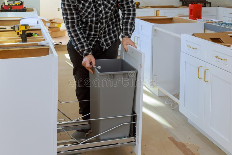 Man hands assembling furniture garbage bin in the kitchen. At his new home drawers cabinet screwdriver installation installing wood repair work carpenter tool stock photos