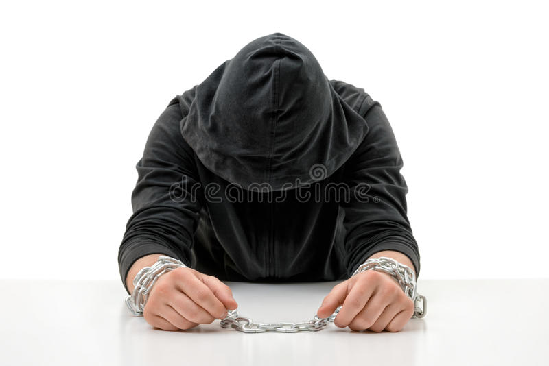 Man with hands in chains is sitting head bowed. Crime and punishment. Offense against the law. Guilt and remorse. Offender in captivity. Restraint of liberty stock images