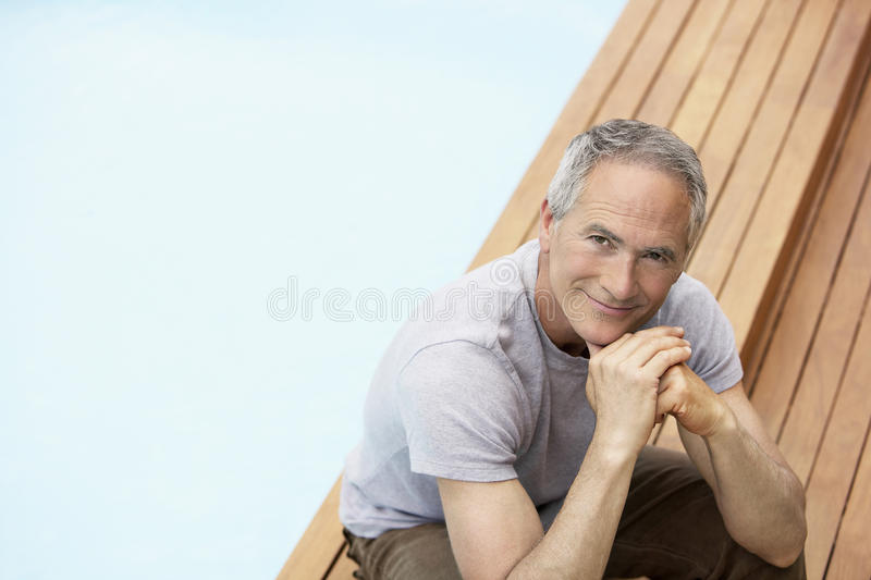Download Man With Hands On Chin Relaxing By Pool Royalty Free Stock Image - Image: 31833966