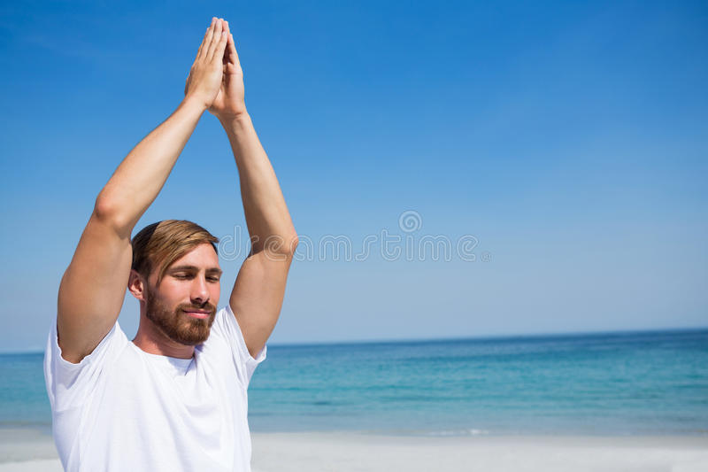 Man with hands clasped exercising at beach royalty free stock photography