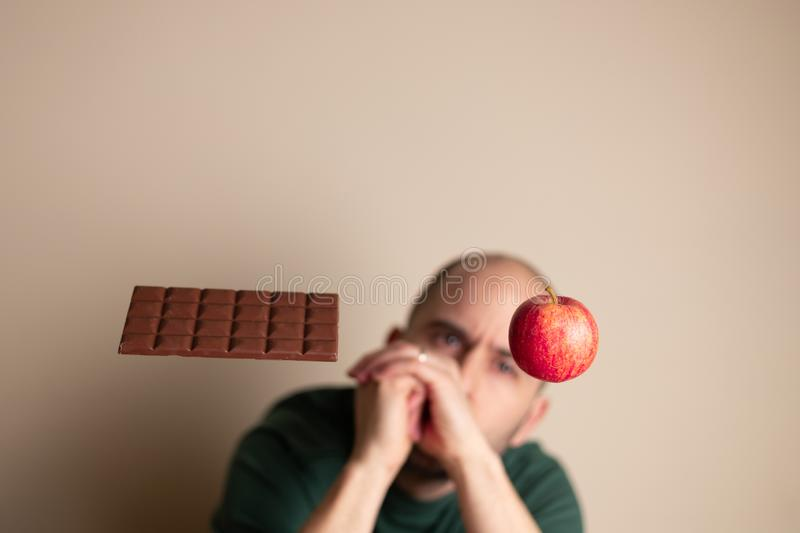 Man with hands closed looking at an apple that is levitating next to a chocolate bar royalty free stock photos