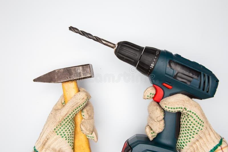Man hands with cordless drill and hammer on white background stock image