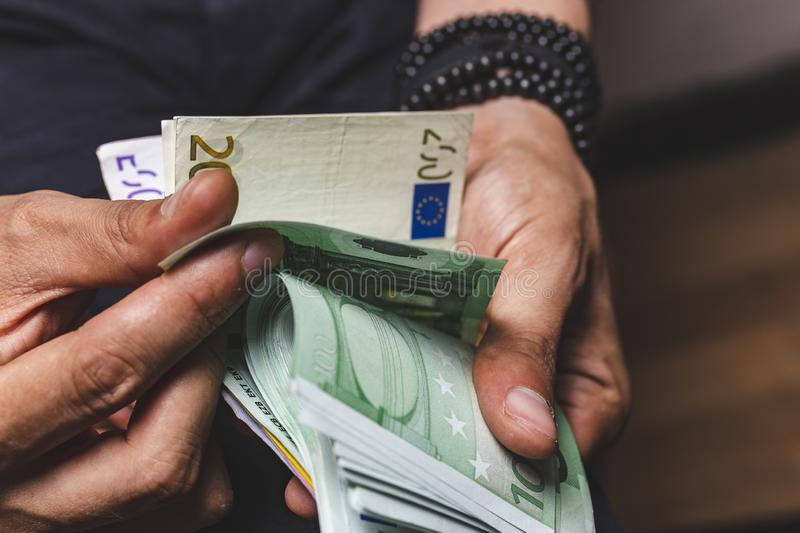 Man hands counting large amount of euro currency cash banknotes. Symbol, path, dollar, payment, wealth, bill, account, growth, transaction, finance, business stock photography