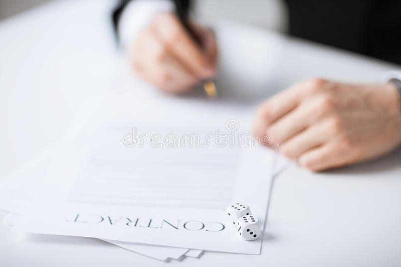 Man hands with gambling dices signing contract stock images