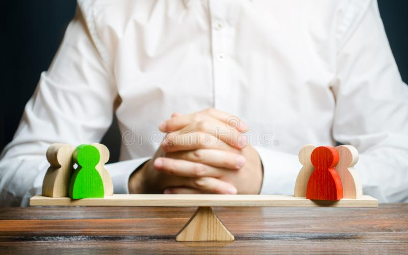 A man with hands in the gesture of a lock and looks at the red and green standoff groups on a scales. conflict resolution. And the search for a compromise in stock image