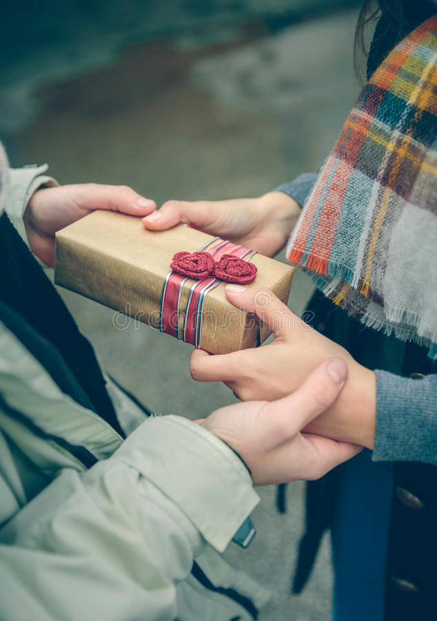 Man hands giving gift box to woman with scarf royalty free stock image