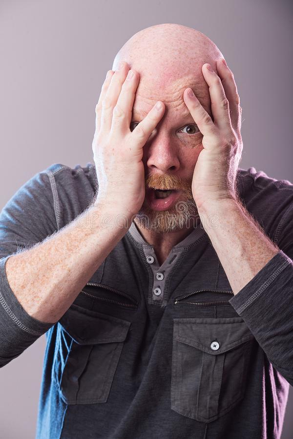 Shocked man with expression of disbelief. Man with hands on his face with expression of shock and disbelief royalty free stock image