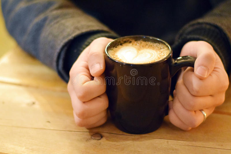 Man hands holding a cappuccino. In a coffee mug in a cafe royalty free stock image