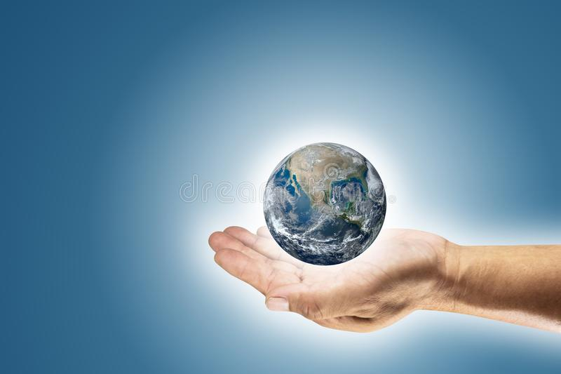 Man hands holding earth with blue background. Element of this image furnished by NASA. stock photo