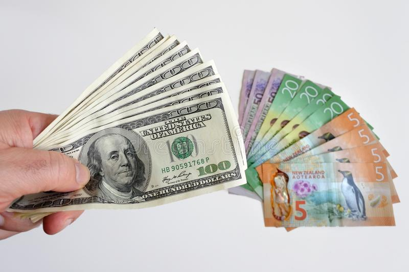 Man hands holding firmly many hundred of US Dollar currency notes against New Zealand currency bills. Money concept. Savings, Investment, Crises, Economy. Copy royalty free stock photography