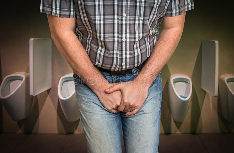 Man with hands holding his crotch, he wants to pee. In restroom - urinary incontinence concept stock photos