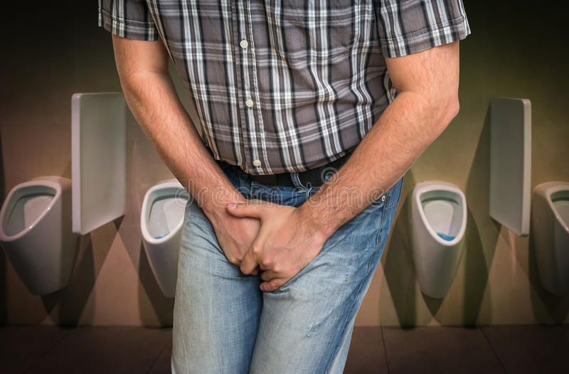 Man with hands holding his crotch, he wants to pee. In restroom - urinary incontinence concept stock image