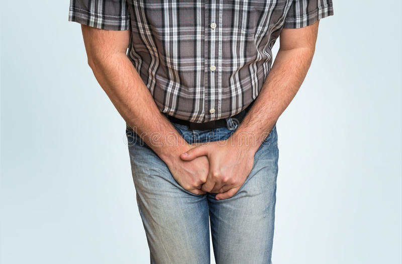 Man with hands holding his crotch, he wants to pee. Urinary incontinence concept stock photos