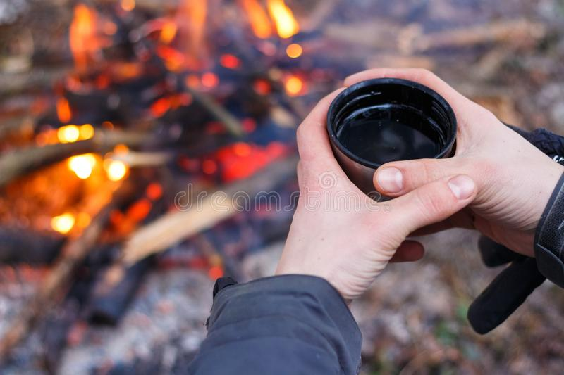 Man hands holding cup near the fire royalty free stock photos