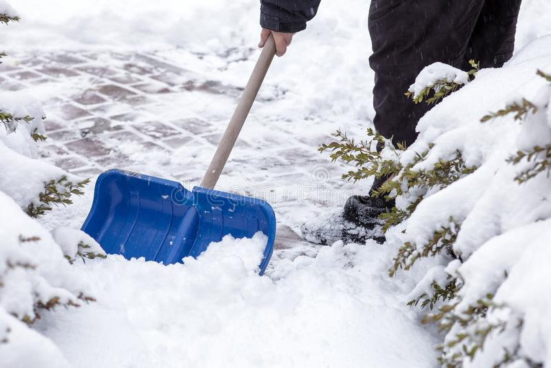 Man hands holding shovel and working with snow on the yard. royalty free stock images
