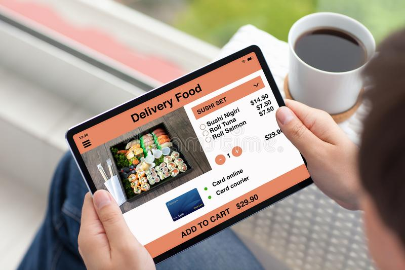 Man hands holding tablet computer with app delivery food stock images