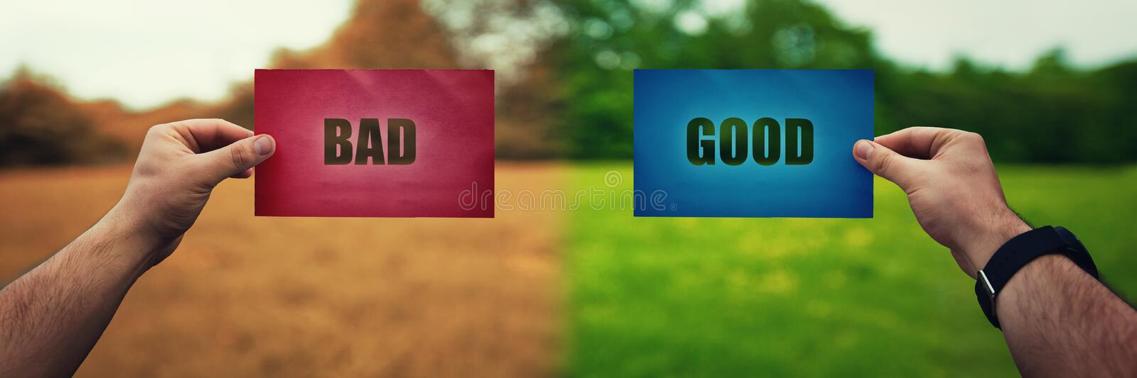Man hands holding two colored paper sheets with opposite text good and bad over different nature environment background. Life stock photo