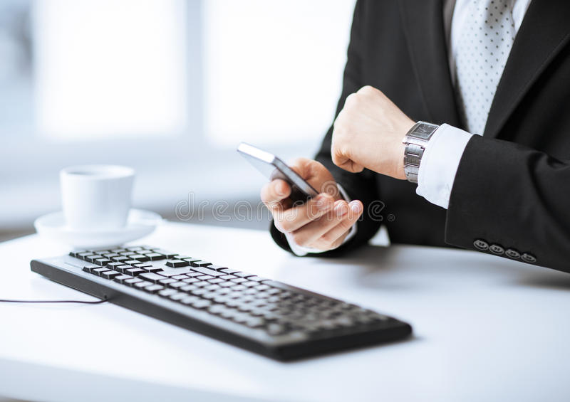 Man hands with keyboard, smartphone and wristwatch royalty free stock images