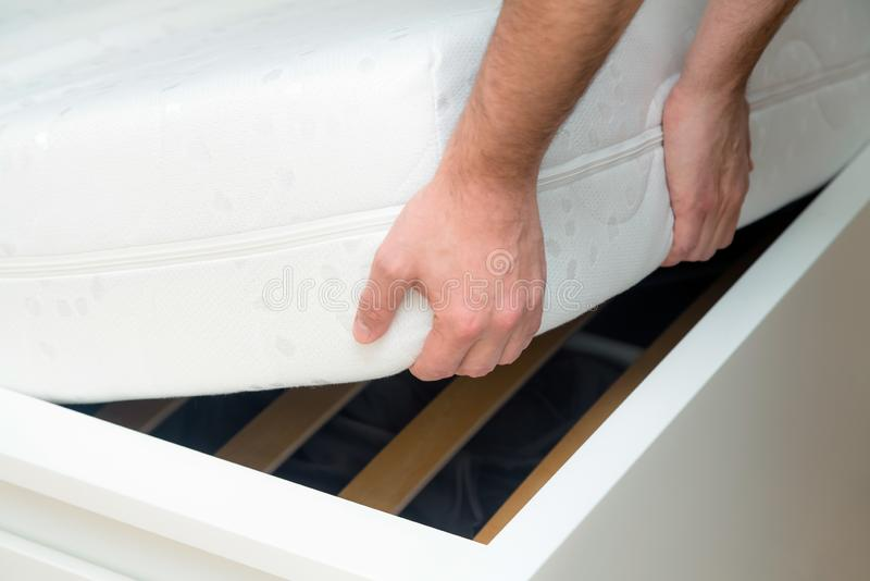 Man hands lifting the mattress at the bedroom. Looking at the bed frame, inspects the mattress royalty free stock images