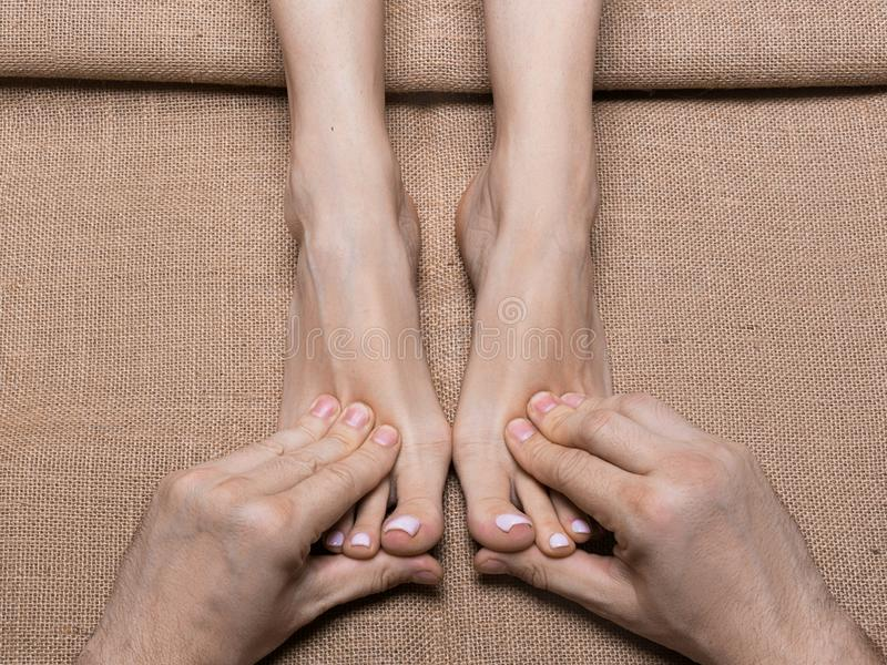 Man hands massaging woman`s feet on canvas. Spa salon. stock photo