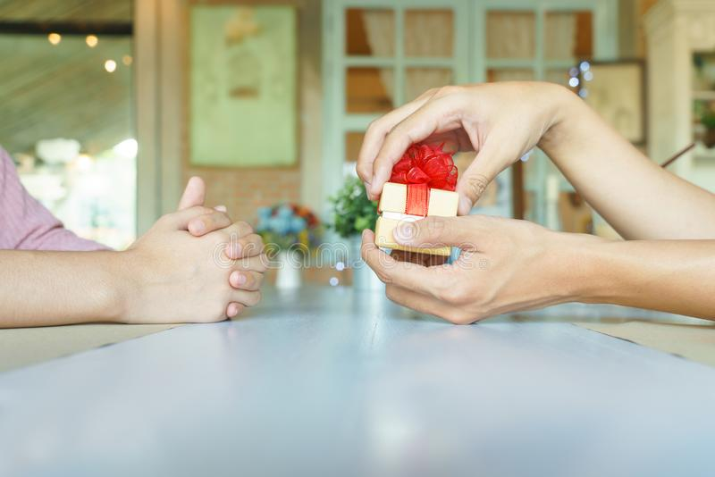 Man hands opening a golden present box with red ribbon to give h. Is lover in restaurant royalty free stock photography