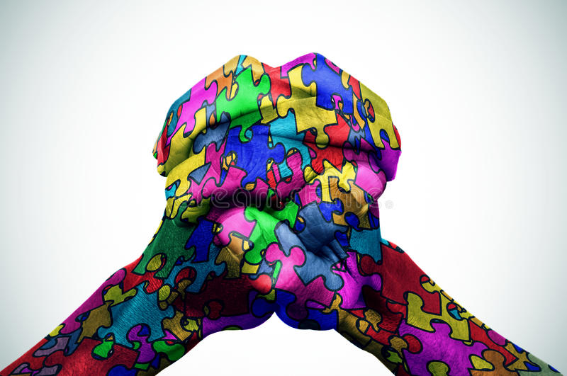 Man hands patterned with puzzle pieces of different colors stock images
