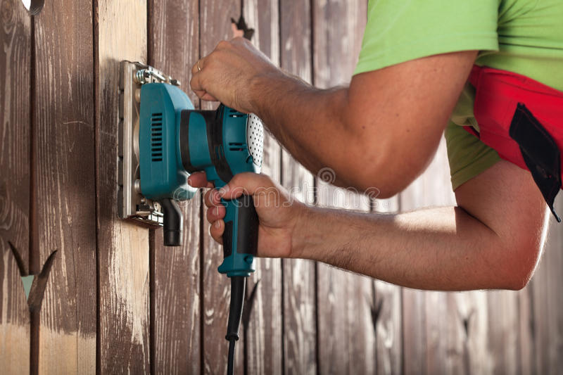 Man hands polishing old fence with power tool royalty free stock photo