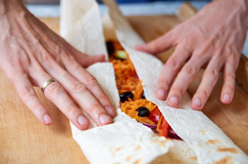 Man hands preparing food - vegetarian burrito with vegetables, olives, carrot, bell pepper, tomatoes close up on wooden background royalty free stock photo