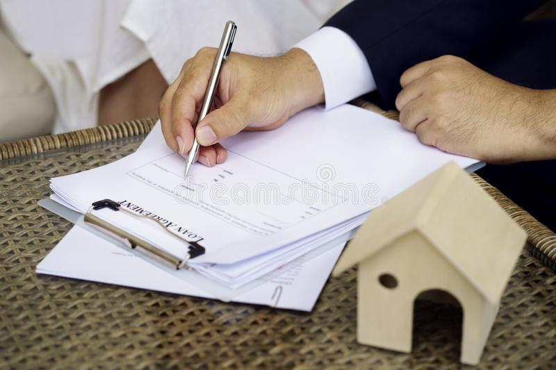 Man hands putting signature on document loan agreement, contract stock photos
