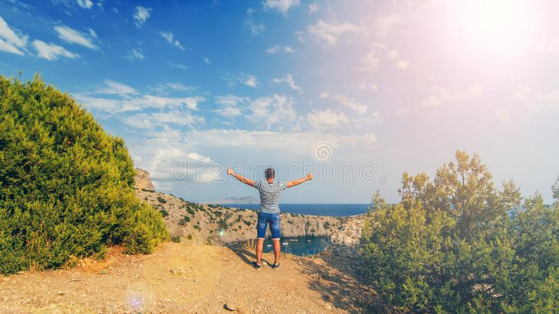 Man with hands raised outdoors in summer on the background of the sea on the top of the mountains stock photo