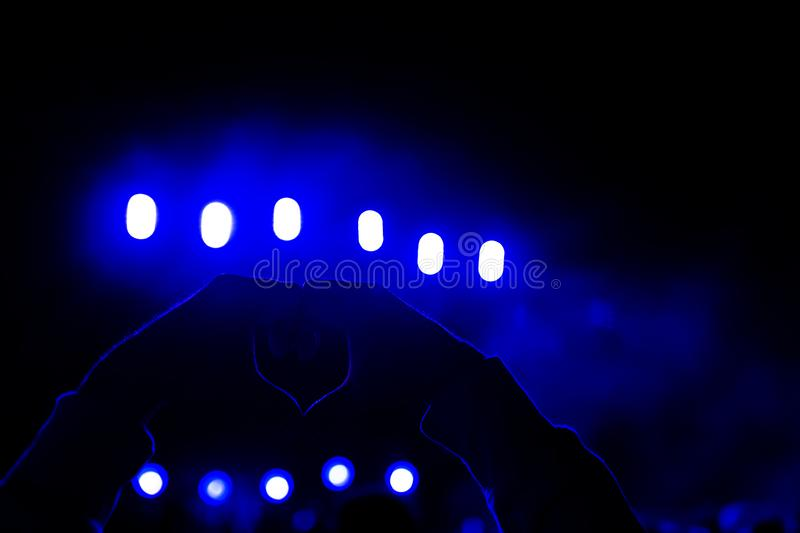 Man hands in shape of heart up in the air. Concert or festival at night concept. LIfestyle outdoors. blue nackground.  royalty free stock images