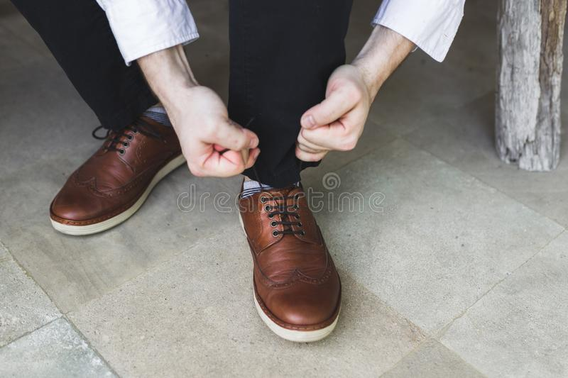 Man hands ties up shoelaces of brown leather shoes. Casual business style royalty free stock images