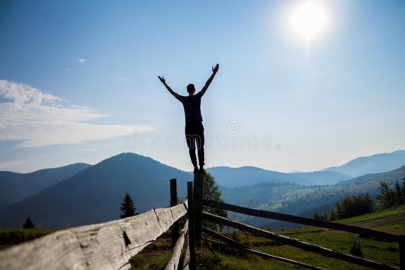 Man with hands up on top of mountains stock photography