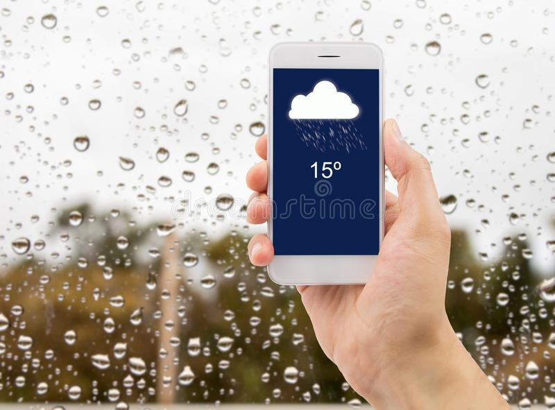Weather forecast in my smartphone. Man hands using mobile phone with glass window full of water droplets of raining day view with weather forecast widget mobile royalty free stock photography
