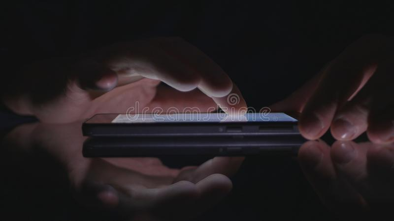 Man Hands Using Cellphone Wireless Application in Darkness stock photography