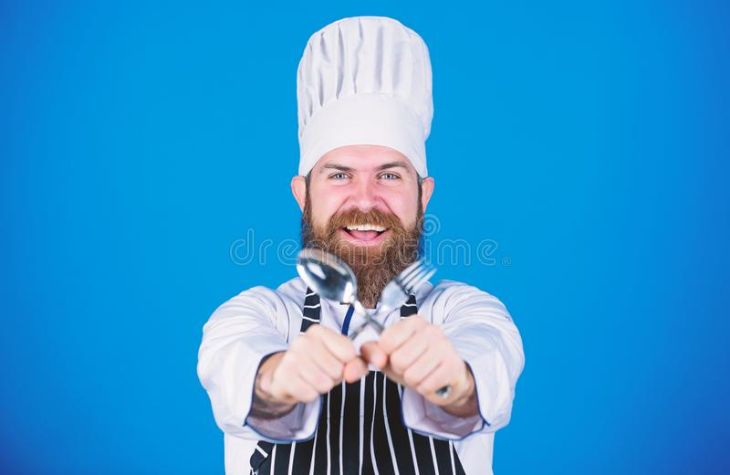Man handsome with beard holds kitchenware on blue background. Cooking process concept. Lets try dish. Hungry chef ready. To try food. Time to try taste. Chef royalty free stock photo
